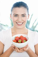 Young woman holding a bowl of strawberries