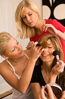 Close-up of a young woman getting make-up put on her face by her friends