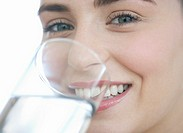 Close up of young woman drinking a glass of water