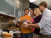 Young man washing dishes and his friends standing behind him with stacks of dishes