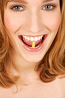A woman holding a capsule between her teeth