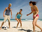 People playing football on the beach