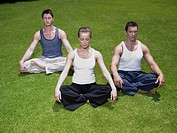 Young woman and two young men meditating on a lawn