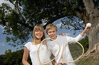Brother and sister holding tennis rackets