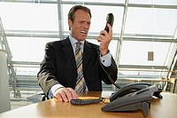Businessman holding a telephone receiver and shouting