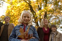 Young girl holding autumn leaves with family