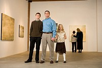 Family standing in art gallery together