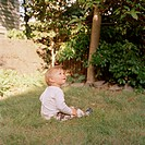 Young child sitting in grass