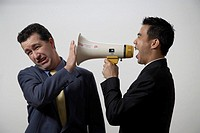 Businessman screaming through megaphone at co-worker