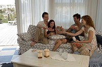 Two couples using playing cards on sofa