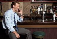 Businessman talking on cell phone at bar