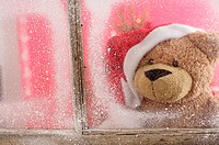 Teddy bear wearing Santa Claus hat looking out of a window (thumbnail)