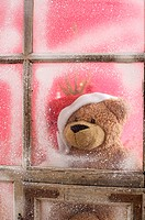 Teddy bear wearing Santa Claus hat looking out of a window