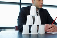 Stacked plastic cups, businessman sitting in background