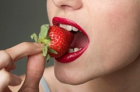 Young woman with red lips eating a strawberry part of, close-up