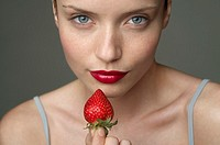 Young woman with a red strawberry under her red lips part of, close-up