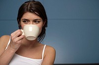 Young woman drinking from a cup, portrait