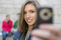 Young woman photographing herself with a mobile phone
