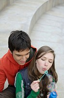 Young couple blowing soap bubbles