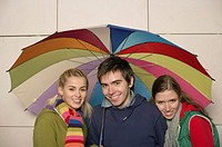 Group of young people under an umbrella