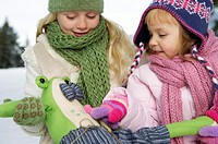 Two girls with a toy animal in snow