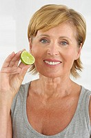 Senior woman holding a slice of lime