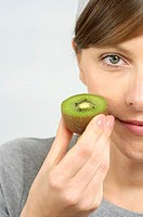 Mid adult woman holding a kiwi fruit