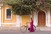 A woman passing by a Pondicherry's house, same colors as the bougainvillea. India