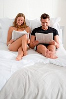 Couple reading newspapers on bed