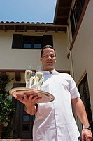 Man holding tray of champagne