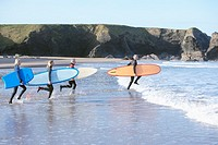 Four adults with surfboards running into the water