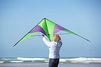 a senior woman with a kite at the beach