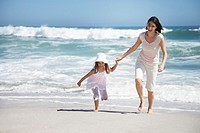 A mother and daughter running on the beach