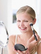 Woman smiling and applying makeup with cosmetic brush and compact mirror