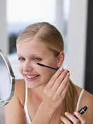 Smiling woman applying mascara in mirror