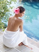 Woman by a pool with a white towel around her