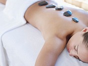 Woman relaxing with massage stones on her back