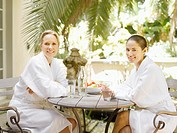 Two women in bathrobes sitting at a table outdoors