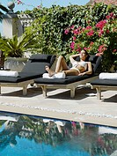 Woman sun tanning in a lounge chair by a pool