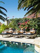 Three women sun tanning in lounge chairs by a pool