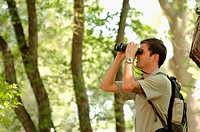 Young man in woods w/binoculars, Regina, Saskatchewan