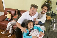 Caucasian dad helping 6 year old Mulatto girl with her arithmetic 1 5 year Mulatto boy with AA mom on sofa 3 year old girl with dad on counter