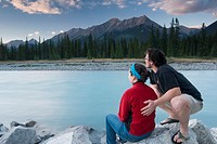 A couple enjoys the sunset from the banks of The Kootenay River in Kootenay National Park