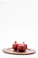 3 pomegranates on wooden plate