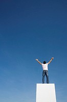 Man standing on pedestal or wall with arms up and blue sky (thumbnail)