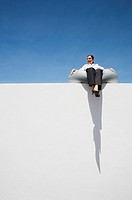 Businesswoman sitting on beanbag chair on wall outdoors (thumbnail)