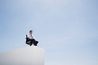 Businessman in office chair on wall outdoors with blue sky