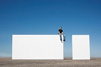 Man sitting on wall outdoors