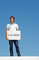 Man holding sign reading Caution outdoors