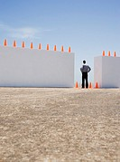 Businessman standing between two walls outdoors with traffic cones